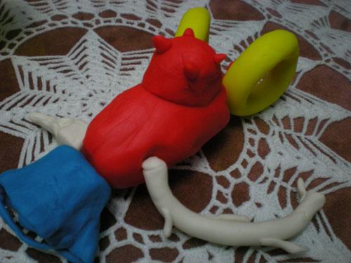 Cabeza de Cubo, cuerpo de vaca, un brazo de una rama de árbol, una mano de un hacha al revés y los piés son dos enormes anillas de calamar.